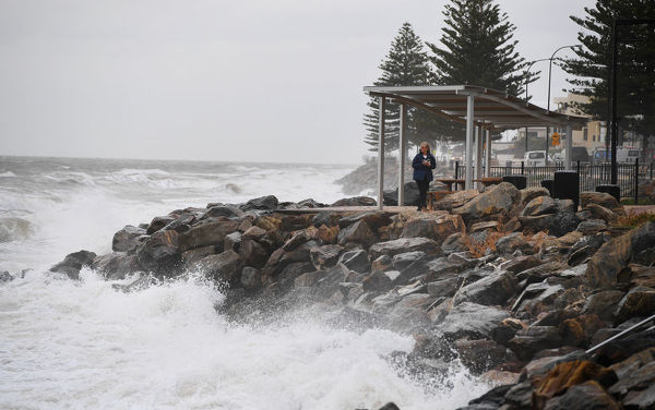 A woman takes a photo of the high tide and a storm surge at Brighton Jbeach as a storm front starts to hit Adelaide's coast line Thursday,June 14th,2018.(Image AAP/Mark Brake)