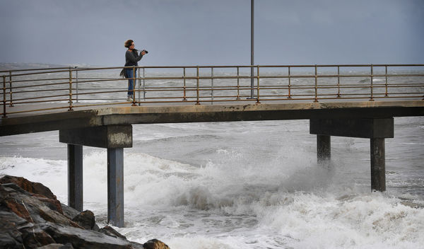 A woman takes a photo of the high tide and a storm surge at Brighton Jetty as a storm front starts to hit Adelaide's coast line Thursday,June 14th,2018.(Image AAP/Mark Brake)