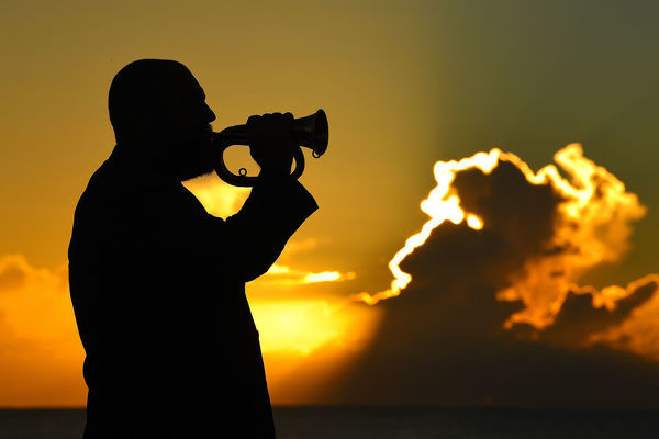 Adam Turner plays the bugle at sunrise on Currumbin Beach on the Gold Coast, Tuesday, April 24, 2018. Turner will play the Bugle at the Anzac Day Dawn Service at Elephant Rock on Currumbin Beach tomorrow. (AAP Image/Dave Hunt)