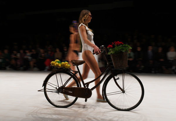 A model pushes a bicycle while wearing a creation by Duskii during the Swim show during the Mercedes-Benz Fashion Week Australia in Sydney, Monday, May 14, 2018. (AAP Image/David Moir), EDITORIAL USE ONLY