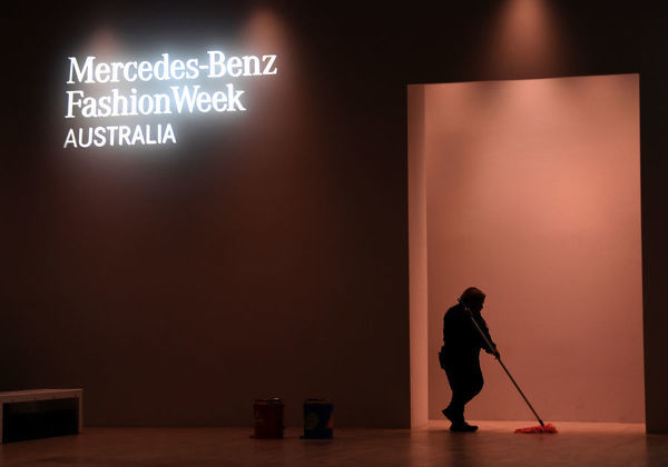 A cleaner mops the floor before the Pereira Fitzgerald show during the Mercedes-Benz Fashion Week Australia in Sydney, Tuesday, May 15, 2018. (AAP Image/David Moir), EDITORIAL USE ONLY