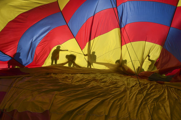 People help pack up a hot air balloon during the 2015 Canberra Balloon festival in Canberra
