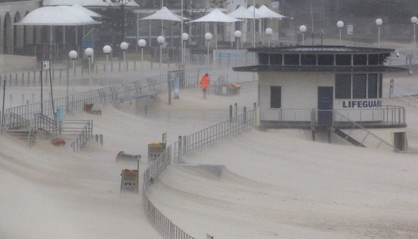 The Bondi Beach promenade is covered in sand blown inland during heavy storms in Sydney
