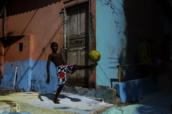 A local kid plays football in an alleyway in the favela of Jaburu in Vitoria, Brazil