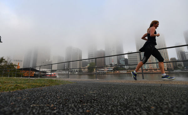 The Brisbane CBD is seen enveloped in a thick fog from Kangaroo Point in Brisbane, Friday, June 29, 2018. The fog has caused flight delays at Brisbane Airport and delays on the Brisbane River CityCat ferries system. (AAP Image/Darren England)