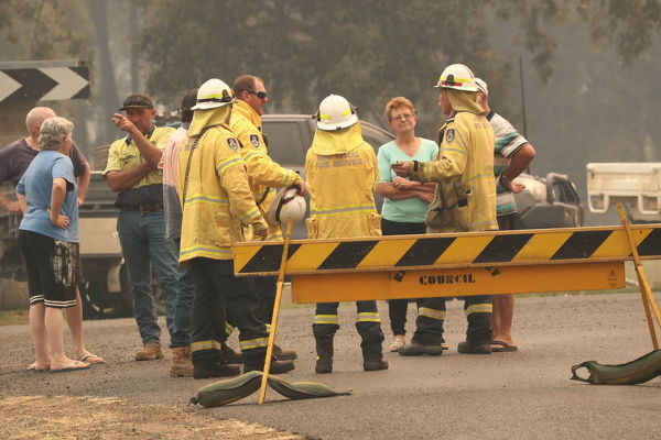 Firefighters are seen talking to local residents near a bushfire burning in Busbys Flat, northern NSW, Wednesday, October 9, 2019. (AAP Image/Jason O'Brien) NO ARCHIVING