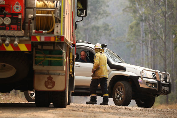 **RE-TRANSMISSION** Firefighters are seen talking to local residents near a bushfire burning in Busbys Flat, northern NSW, Wednesday, October 9, 2019. (AAP Image/Jason O'Brien) NO ARCHIVING