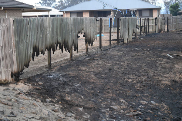 Fire damaged fences are seen in Laidley, southeast Queensland, Wednesday, October 9, 2019. A massive fire bearing down on Laidley in Queensland's Lockyer Valley is believed to have claimed at least one house. (AAP Image/Scott Davis) NO ARCHIVING