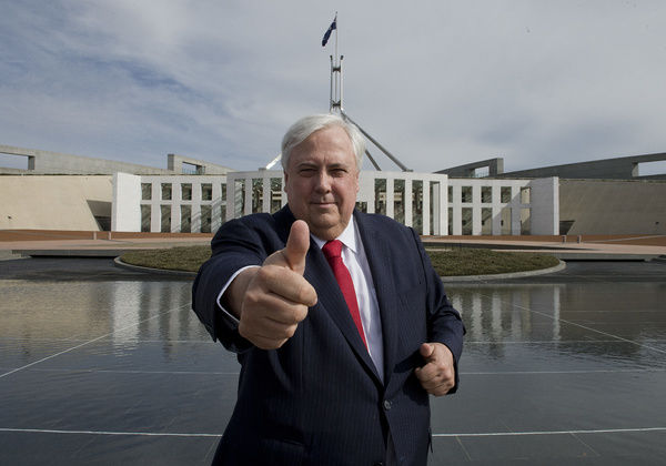 Palmer United Party (PUP) leader Clive Palmer gives a thumbs-up outside parliament house as he waits to do a television interview in Canberra