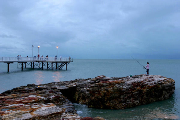 Darwin locals on the Nightcliff fore-shore as the huge weather system associated with Cyclone Ingrid obscures the sunset