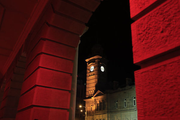 The Hobart Town Hall and the GPO are coloured red as Hobart's Macquarie St is excavated to release artist Mike Parr during Tasmania's Dark Mofo festival in Hobart, Sunday, June 17, 2018. (AAP Image/Rob Blakers)