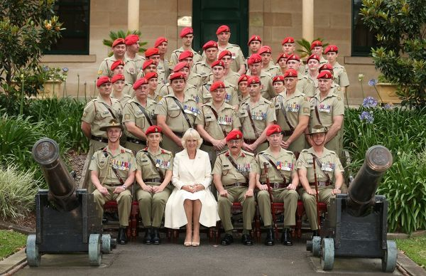 Britain's Camilla, Duchess of Cornwall, sits next to Military Police while posing for a group photograph at Victoria Barracks in Sydney