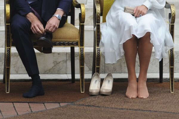 Prince William, Duke of Cambridge and his wife Catherine, Duchess of Cambridge take off their shoes before visiting the Assyakirin Mosque in Kuala Lumpur