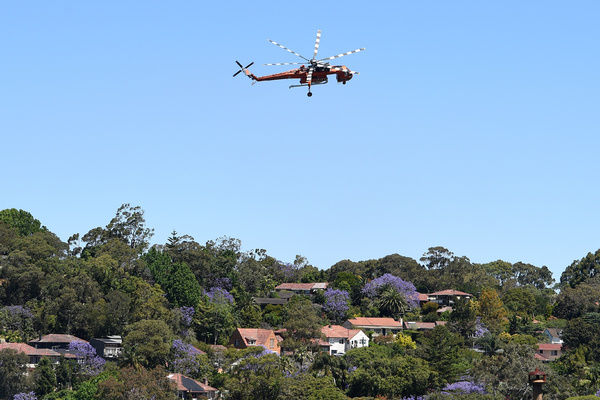 An Erickson Skycrane prepares to drop water on a bushfire near homes in Castle Cove, Sydney