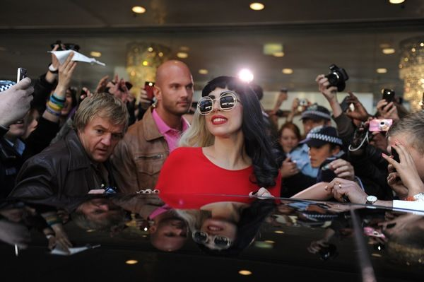 Screaming fans crowd around American singer Lady Gaga as she leaves her hotel in the CBD, Sydney