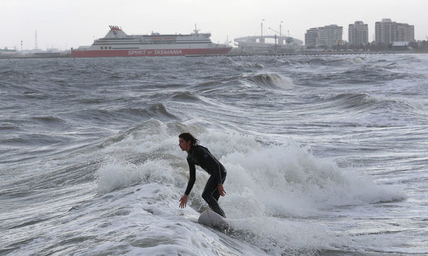 A surfer catches a wave in the usually calm waters of Port Phillip bay in Port Melbourne as wild weather sweeps across the city in Melbourne, Sunday, June 17. 2018. (AAP Image/David Crosling)