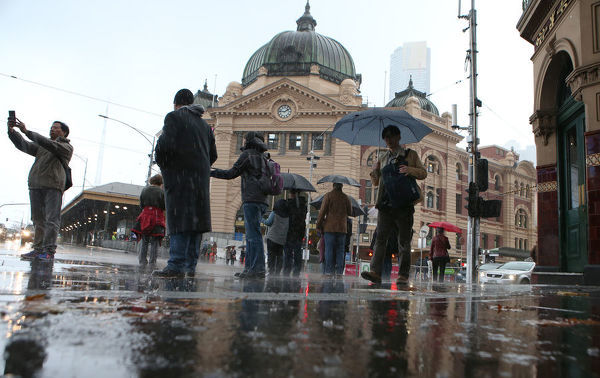 Pedestrians are are seen in wild weather outside Flinders Street Station in Melbourne, Sunday, June 17. 2018. (AAP Image/David Crosling)