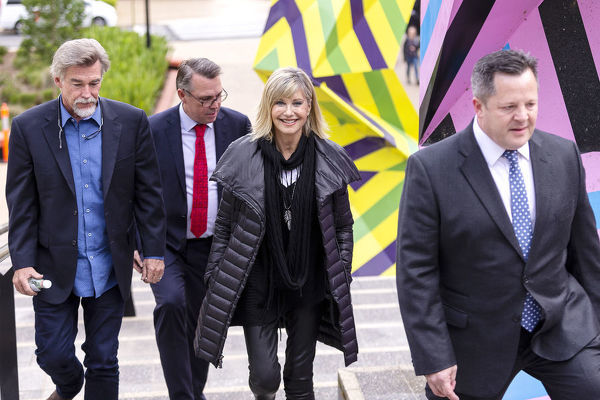 Olivia Newton-John arrives with husband John Easterling (left) ahead of a special graduation ceremony at La Trobe University, Union Hall, Melbourne, Monday, May 14th, 2018. (AAP Image/Daniel Pockett)