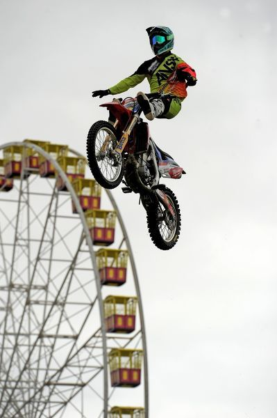 A man performs a stunt on a bike in the lead up to the opening of the annual Royal Melbourne Show in Melbourne. (AAP Image/Joe Castro)