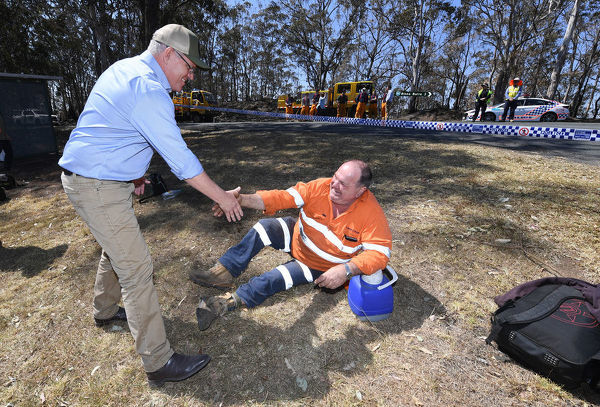 Australian Prime Minister Scott Morrison shakes hands with an emergency services worker taking a rest during a visit to the bushfire affected area of Binna Burra in the Gold Coast Hinterland, Friday, September 13, 2019