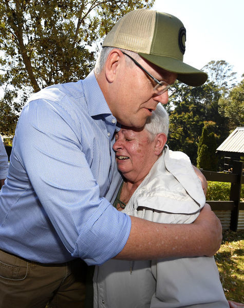 Australian Prime Minister Scott Morrison consoles Pamela Skeen who had lost her home at the bushfire affected suburb of Binna Burra in the Gold Coast Hinterland, Friday, September 13, 2019. Bushfires claimed scores of homes in Queensland
