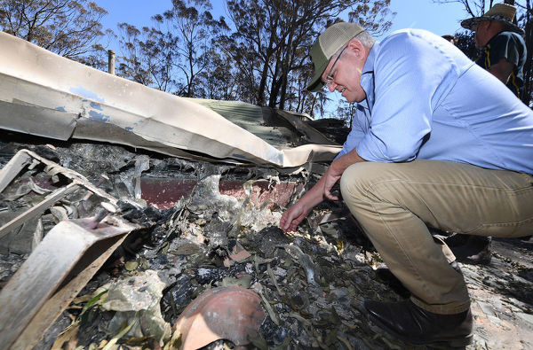 Australian Prime Minister Scott Morrison sifts through remains of a home during a visit to the bushfire affected area of Binna Burra in the Gold Coast Hinterland, Friday, September 13, 2019. Bushfires claimed scores of homes in Queensland