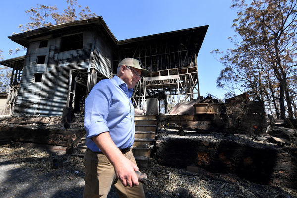 Australian Prime Minister Scott Morrison walks past a burnt out home during a visit to the bushfire affected area of Binna Burra in the Gold Coast Hinterland, Friday, September 13, 2019