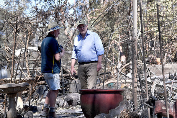Australian Prime Minister Scott Morrison is seen inspecting the burnt out property of Stuart Skeen (left) at Binna Burra in the Gold Coast Hinterland, Friday, September 13, 2019. Weather conditions have eased after severe bushfires claimed scores of homes in Queensland