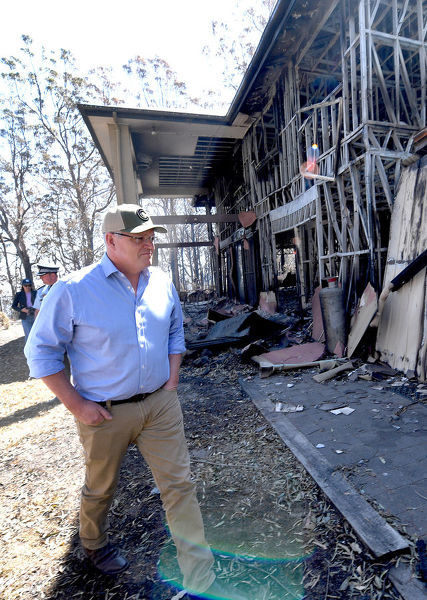 Australian Prime Minister Scott Morrison is seen inspecting a burnt out property at Binna Burra in the Gold Coast Hinterland, Friday, September 13, 2019. Weather conditions have eased after severe bushfires claimed scores of homes in Queensland