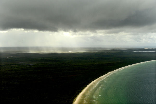Storm Fraser Island. Sunlight breaks through a rain storm above Fraser Island