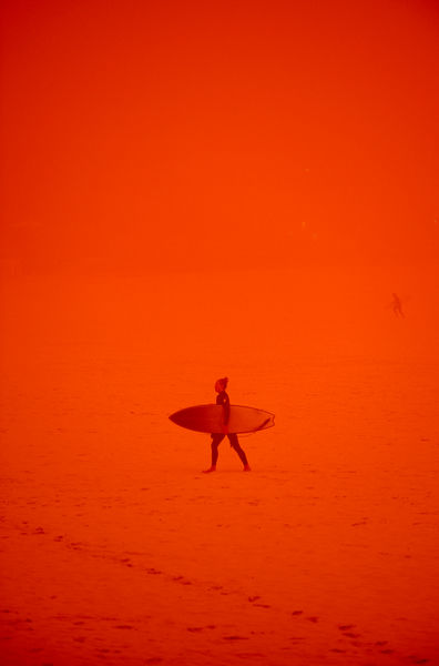 A surfer walks up the sand in a dust storm at Bondi Beach in Sydney