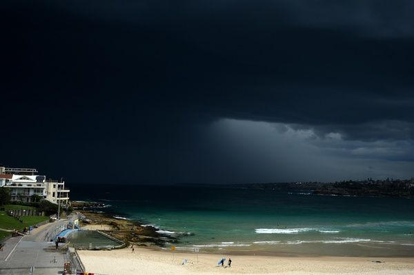 Surfers are seen leaving the water as storm clouds build over Bondi beach, in Sydney