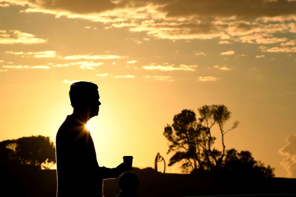 A man drinks a coffee as the sun rises in Coogee, Sydney, Thursday, July 12, 2018. (AAP Image/Joel Carrett)