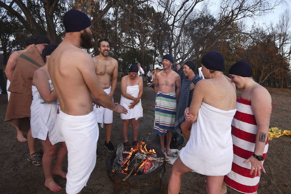 Participants of the Winter Solstice Nude Charity Swim warm up next to a fire pit after swimming in the waters of Lake Burley Griffin in Canberra, Thursday, June 21, 2018