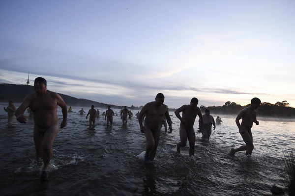 Participants of the Winter Solstice Nude Charity Swim get out of the waters of Lake Burley Griffin in Canberra, Thursday, June 21, 2018