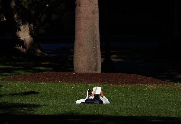 A man lies on his back as he reads a book in Hyde Park in central Sydney, Thursday, May 30, 2019. Australians are facing a drier and warmer than average winter, with much hoped for rain unlikely to fall in eastern and central parts of the country