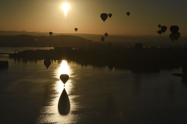 Hot air balloons are seen flying over Lake Burley Griffin during the 2015 Canberra Balloon festival in Canberra
