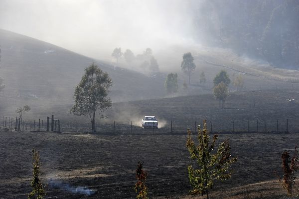 A property owner in car looks over burnt out areas in Kersbrook as fires continue to burn through the Adelaide Hills