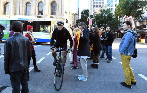 A cyclist makes his way through Extinction Rebellion protestors as they block early morning peak hour traffic in Brisbane, Thursday, July 11, 2019. (AAP Image/Dave Hunt)