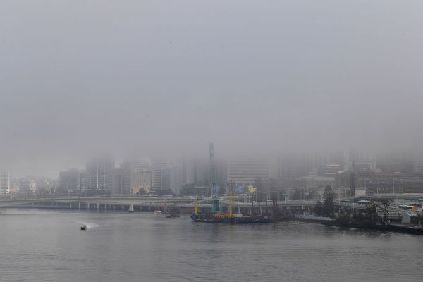 Fog is seen over the Brisbane CBD in Brisbane, Monday, August 19, 2019. The fog caused some flight delays and Brisbane CityCats ferry service on the Brisbane River was suspended until the fog cleared. (AAP Image/Darren England)