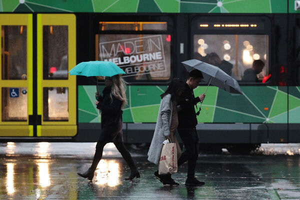 People are seen using umbrellas in the Melbourne CBD on Friday, May 11, 2018. A wild and windy night in Melbourne has produced more rain than the entire month of April and it's not over yet. Damaging winds and rain are expected to return on Friday afternoon