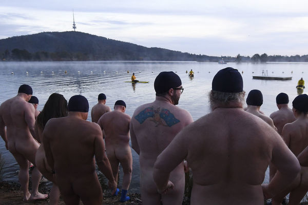 Participants of the Winter Solstice Nude Charity Swim get into the waters of Lake Burley Griffin in Canberra, Thursday, June 21, 2018