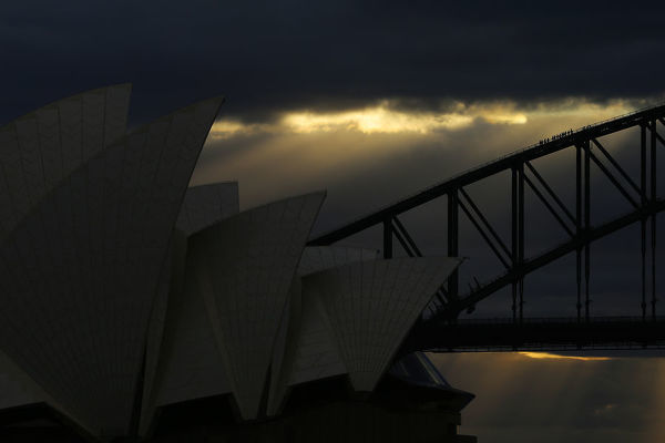 Bridge climbers are seen walking up the arch of the Sydney Harbour Bridge behind the roof of the Sydney Opera House as the sun sets during the winter solstice in Sydney, Saturday, June 22, 2019. (AAP Image/Steven Saphore)