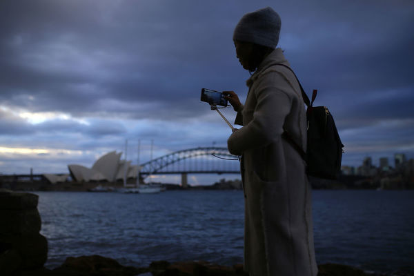 A woman takes photos of the Sydney Harbour Bridge and the Sydney Opera House with her mobile phone during the winter solstice in Sydney, Saturday, June 22, 2019. (AAP Image/Steven Saphore)